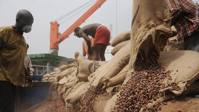 Ivorian workers empty bags of cocoa beans into a container at the Port of Abidjan.