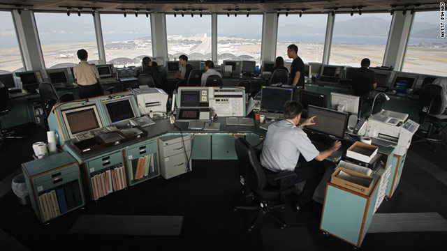 Air traffic controllers monitor flights in the control tower of Hong Kong International Airport.