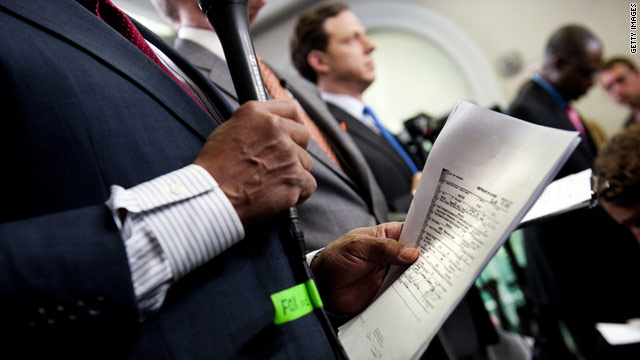 Televison news correspondents hold copies of U.S. President Barack Obama's long-form birth certificate at the White House.