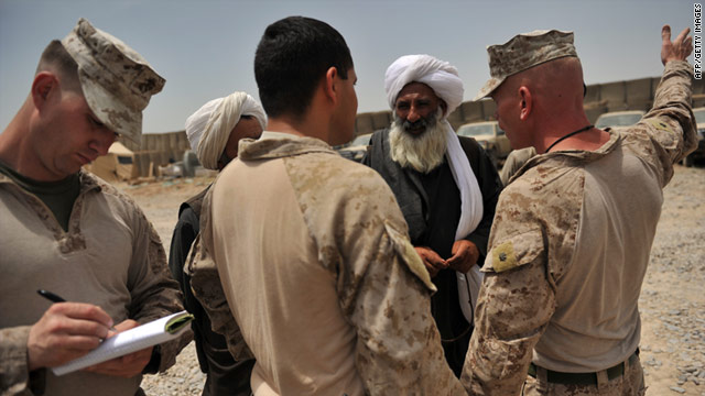 Marine Lt. Col. John Harril talks to a leader in Helmand province, Afghanistan, as 1st Lt. Jake Freeman takes notes.