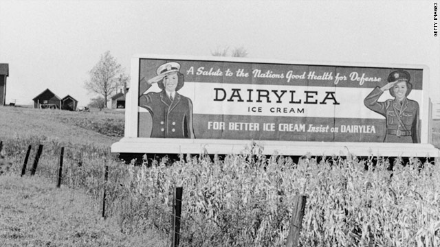 A 1941 photo of a Dairylea Ice Cream billboard in Utica, New York, shows two U.S. servicewomen saluting.