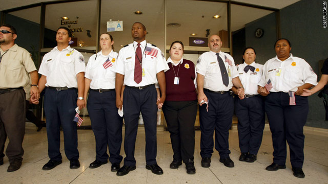 TSA employees hold hands around a memorial to the victims of the September 11 terror attacks at Los Angeles International Airport in 2003.
