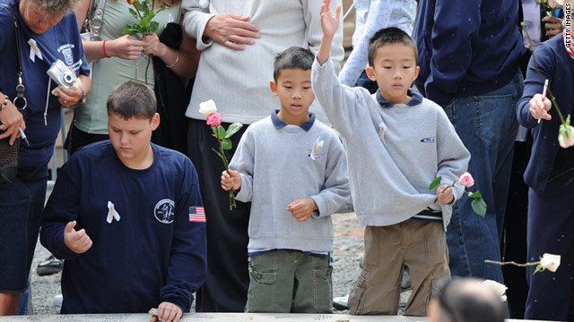 Two boys toss flowers into a pool at a September 11 memorial service at ground zero in 2008