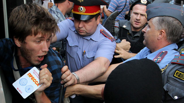 A young man shows his press ID as Russian police detain him at a protest in Moscow on July 31.