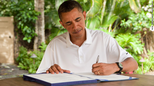 President Barack Obama signs the 9/11 health care bill into law Sunday at his vacation rental in Kailua, Hawaii.