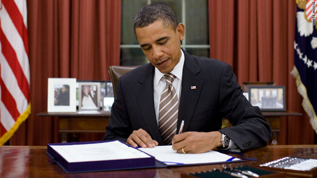 President Obama signs the bill on Tuesday in the White House's Oval Office.