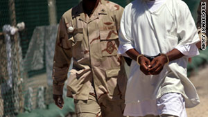 A U.S. military guard moves a detainee held at Guantanamo Bay, Cuba, in 2010.
