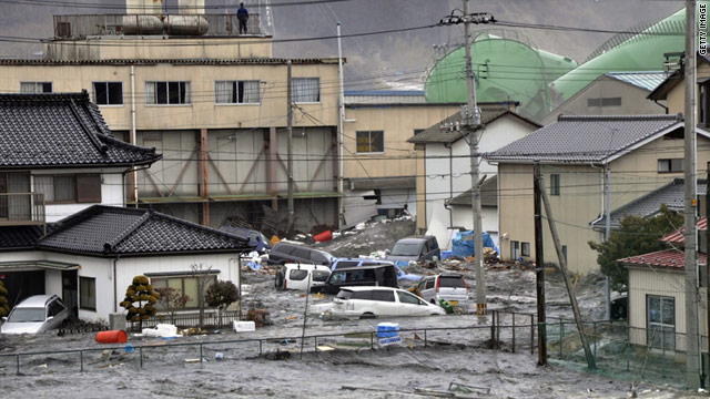Waves from the tsunami smash vehicles and houses in Kesennuma city in Miyagi prefecture, northern Japan.