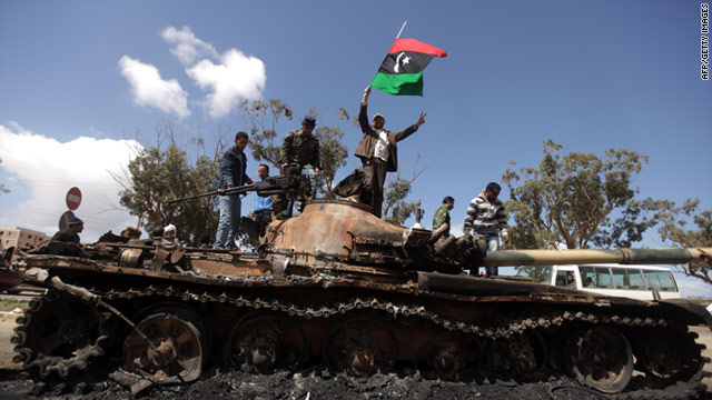 Libyan rebels celebrate atop the burned-out hulk of a loyalist tank Sunday.