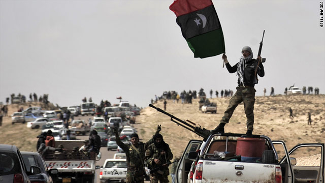 Libyan rebels wave the flag of the rebellion as they gather near Brega March 31.