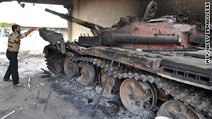 A Libyan man  in Misrata, Libya, in April looks at a government tank destroyed by NATO bombing.