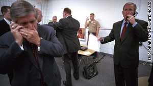 Bush confers on a secure line as &quot;the football&quot; -- the briefcase holding the secure nuclear launch codes -- is watched by a Marine.