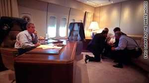 White House advisers plan the route for Air Force One as Bush works in his cabin.