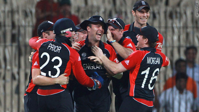 England's cricketers mob Jonathan Trott (c) after his run out sealed a dramatic victory over the West Indies.
