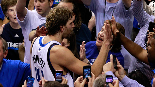 Dirk Nowitzki, the game's leading points taker, celebrates with Dallas fans after their 112-103 win.