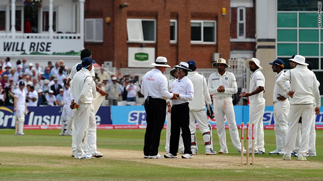 Ian Bell (far left) waits as the umpires discuss India's appeal for a run out. Bell was given out but later reprieved.