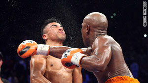Floyd Mayweather Jr. delivers a right to Victor Ortiz in the fourth round of their fight on Saturday.