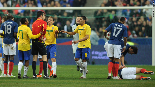 Brazil's players argue with German referee Wolfgang Starck after Hernanes was sent off for a high kick at Karim Benzema.