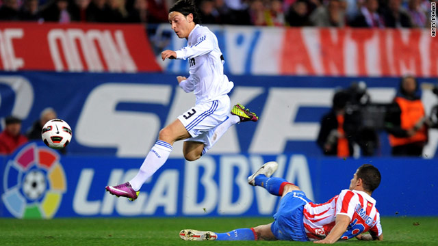 Real Madrid goalscorer Mesut Ozil rides a late tackle by Atletico Madrid's Alvaro Dominguez  in Saturday's derby.