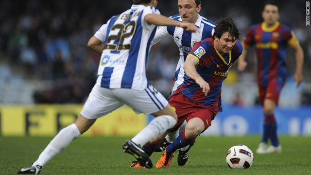 Barcelona's Lionel Messi struggles to break free from the Real Sociedad defense during his team's 2-1 defeat on Saturday.