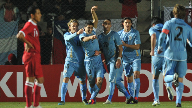 Luis Suarez (arm raised) celebrates the goal that earned Uruguay a 1-1 Copa America draw with Peru.