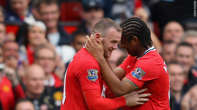 Wayne Rooney (left) is congratulated by team-mate Anderson after completing his hat-trick in the 8-2 rout of Arsenal.