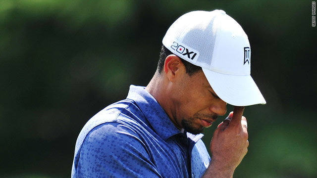 A dejected Tiger Woods contemplates missing the cut for only the third time in a major tournament.
