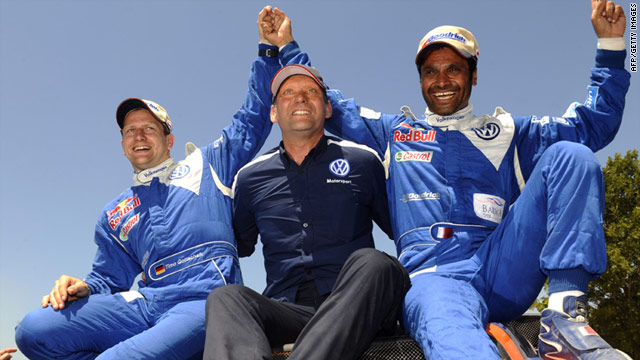 Nasser Al-Attiyah, right, celebrates with co-driver Timo Gottschalk, left, and team manager Chris Niessen.