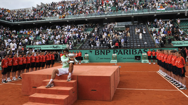 Spain's Rafael Nadal poses with the French Open trophy at Roland Garros after beating Robin Soderling in June 2010.
