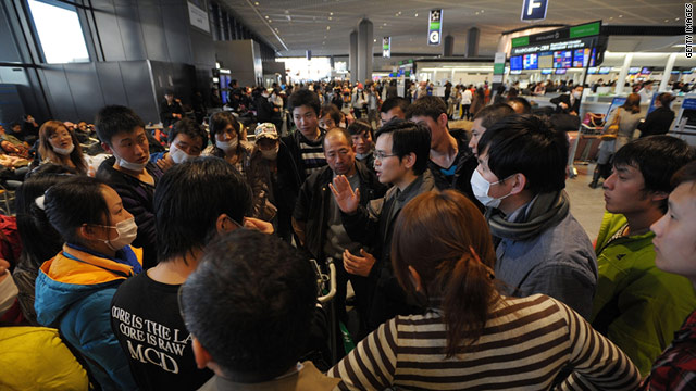 Tourists from China listen to their tour leader Friday at Narita International Airport outside Tokyo, Japan.