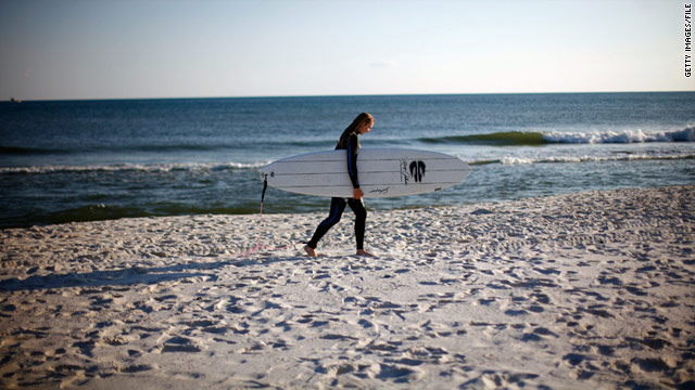 A surfer walks Pensacola Beach, Florida, in March, 2011.