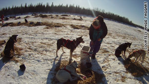 Taggart feeds her dogs at the checkpoint of Rainy Pass.