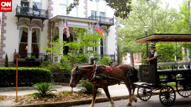 A horse-drawn carriage passes by a historic house in Savannah, Georgia, one of the state's tourist hot spots.
