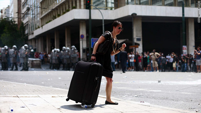 A tourist walks down the sidewalk while protesters line the streets and police stand guard in Greece, on Tuesday.