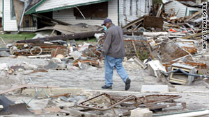 A man on December 1, 2005, walks past debris left by Hurricane Katrina in New Orleans, Louisiana.