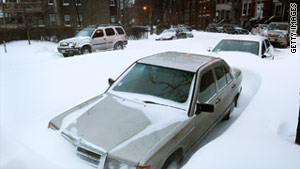 Cars are buried in snow on Wednesday in the Bucktown neighborhood of Chicago.