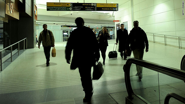 Passengers walk in near darkness at Newark Airport after an electrical failure Monday.