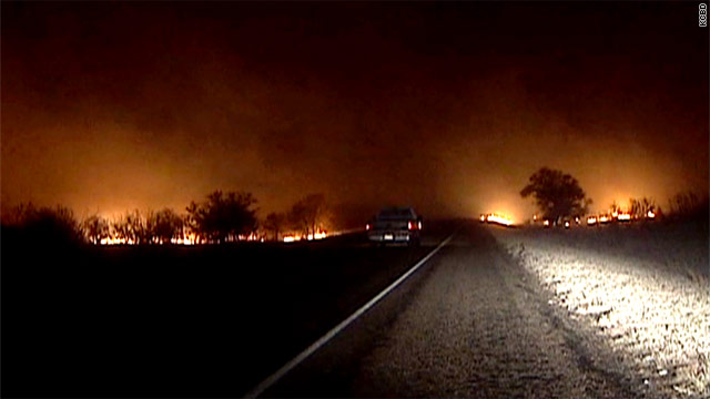 A pickup drives through a fire line Sunday in Matador, Texas, northeast of Lubbock.