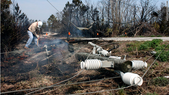 A Florida Power and Light Co. worker this week throws dirt on a smoldering electric pole destroyed in a central Florida blaze.