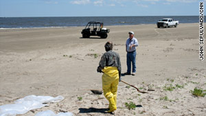 SEACOR's Jim McHale, background, manages oil cleanup workers on Elmer's Island, Louisiana.