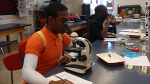 Student Roger Smith Jr. draws what he sees through the microscope at Glenville High School in Cleveland.