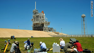 Photographers check their equipment at Kennedy Space Center, Florida, on Saturday.