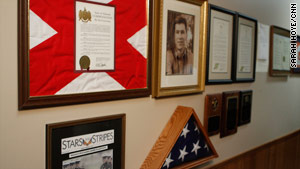 A photo, headline, resolutions and the flag that draped Mike Spann's coffin line the walls of his father's office.