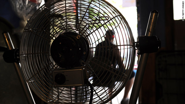 A flag seller in New York's Spanish Harlem uses a fan in his shop Wednesday as temperatures reach record-breaking highs.