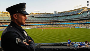 A police officer watches over Dodger Stadium, where attendance is down and where a fan was brutally attacked in the parking lot on opening night.