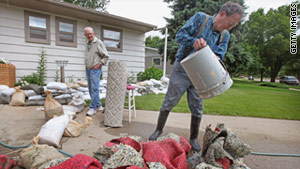 Gordon Valgren, right, cleans debris from his flood-damaged home Monday in Minot, North Dakota.