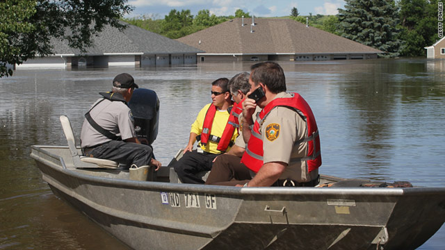 Emergency workers survey flood damage Sunday in Burlington, North Dakota.