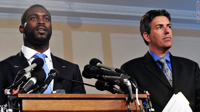 NFL quarterback Michael Vick speaks to reporters with U.S. Humane Society President Wayne Pacelle in Washington.