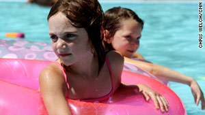 Children in Minneapolis escape the high temperatures by swimming in a public pool at a park.