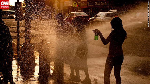 Residents cool off in the fire hydrant water in Queens, New York, to escape the unusually hot weather.